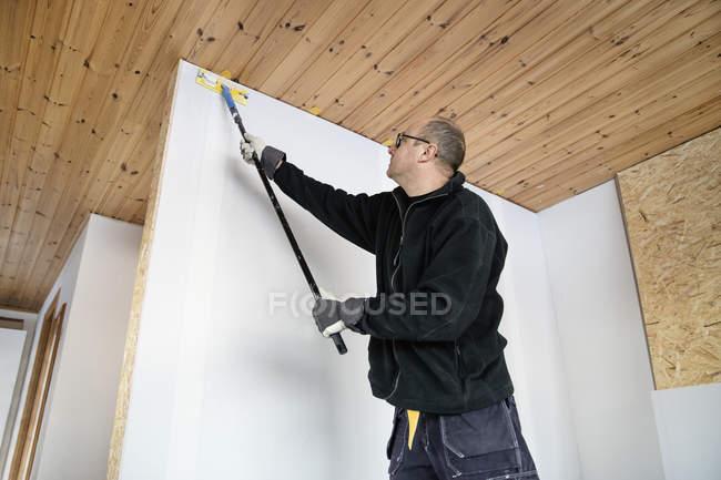 Зрелый человек роспись стены дома — стоковое фото