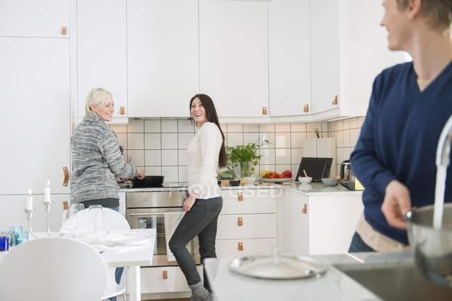 Две женщины и мужчина в семье кухне, сосредоточиться на фоне — стоковое фото