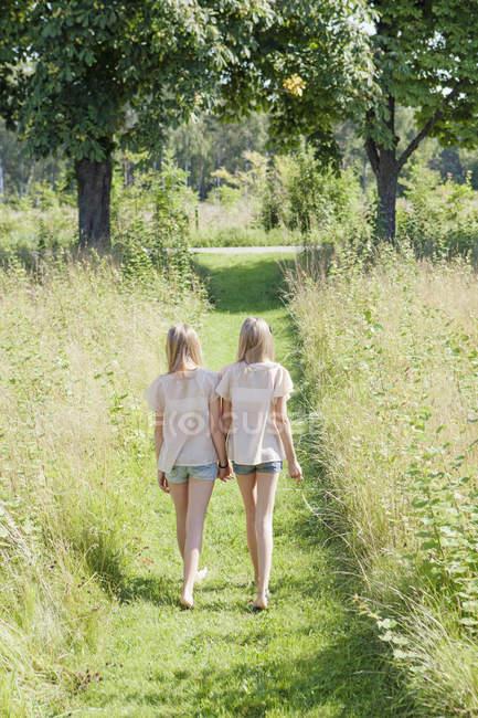 Вид на двух девочек на пешеходной дорожке, вид сзади — стоковое фото