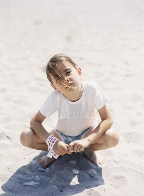 Fille assise sur la plage de sable, foyer sélectif — Photo de stock