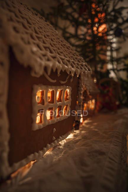 Illuminated gingerbread house beside fir tree — Stock Photo