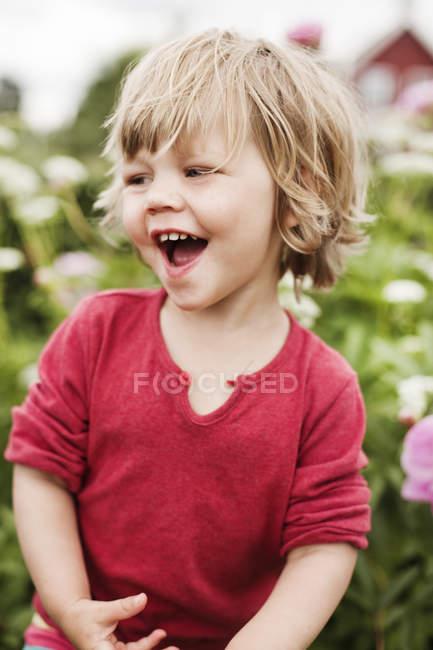 Девушка в саду смеется, сосредоточиться на переднем плане — стоковое фото