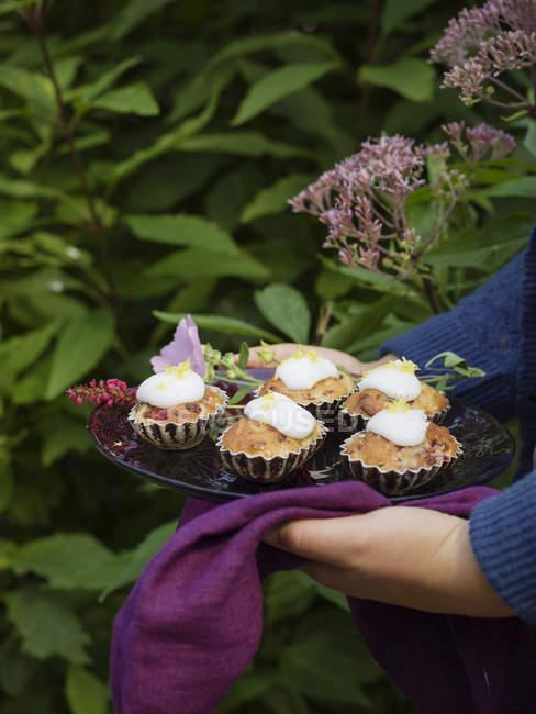 Mulher segurando placa com bolos de ameixa — Fotografia de Stock