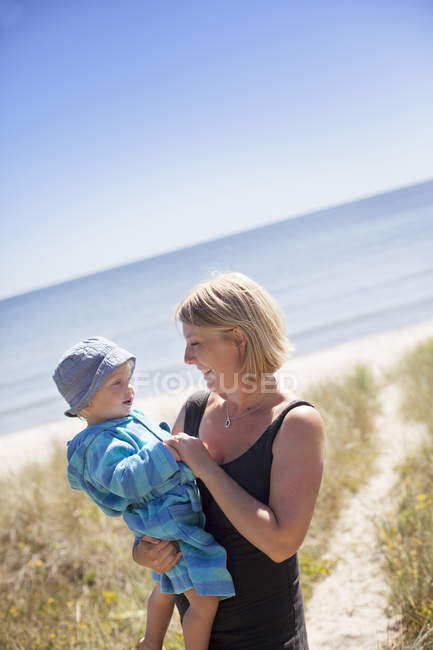 Woman holding son on beach, focus on foreground — Stock Photo