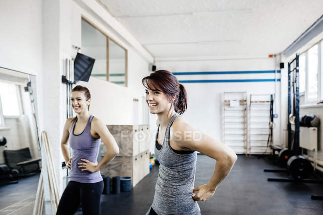 Two young women standing in gym and smiling — Stock Photo