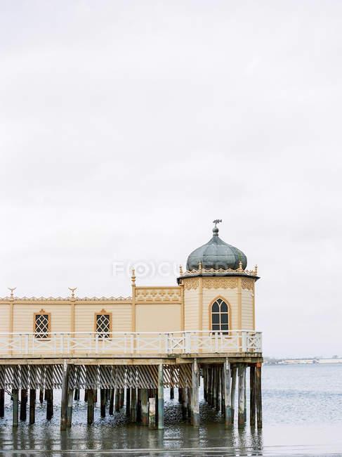 De madeira casa de banhos no mar com céu nublado em fundo — Fotografia de Stock