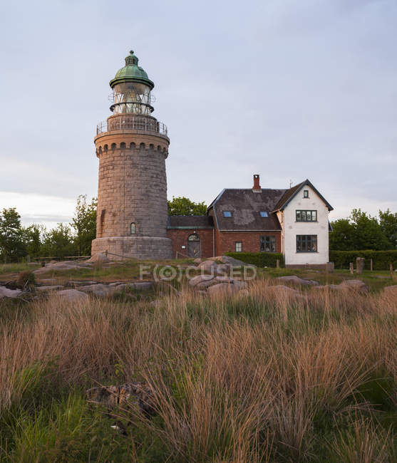Lighthouse building under cloudy evening sky — Stock Photo