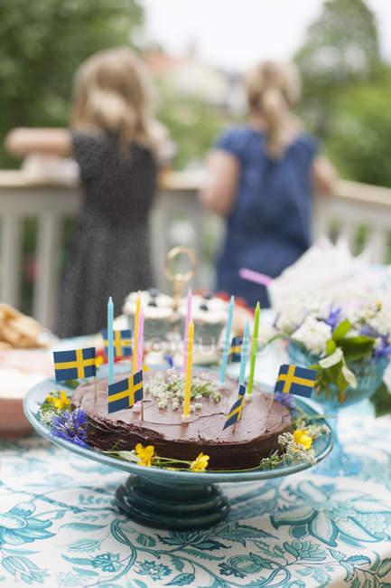 Bolo de aniversário decorado com bandeiras suecas na mesa, meninas no fundo — Fotografia de Stock
