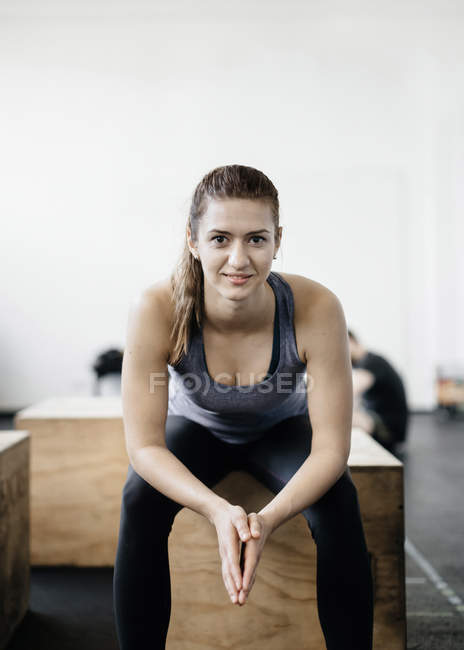 Portrait of young woman sitting on wooden crate in gym — Stock Photo