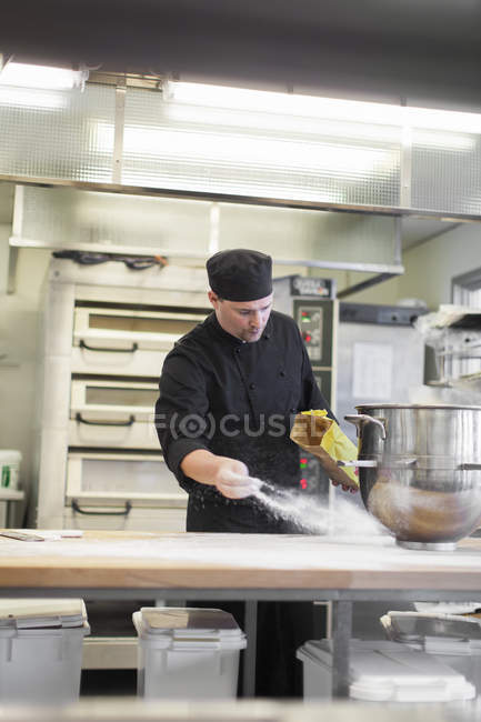 Man in protective workwear working at industrial kitchen — Stock Photo