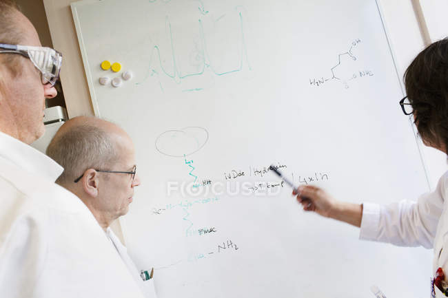 Scientifiques écrivant des formules chimiques sur tableau blanc, accent sélectif — Photo de stock