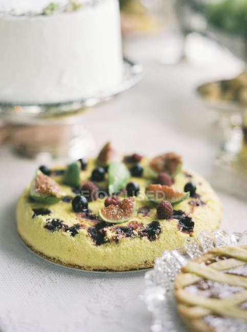 Sweet cake with figs and berries served on table — Stock Photo