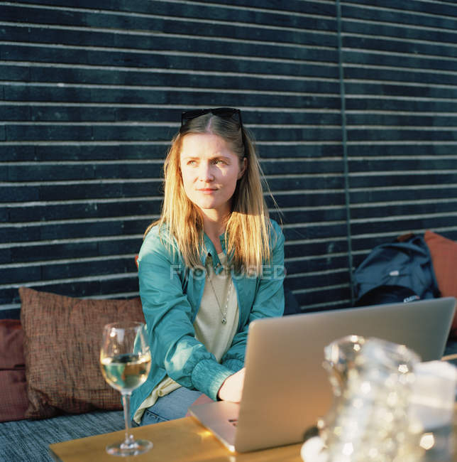 Woman with glass of white wine using laptop on summer terrace, focus on foreground — Stock Photo