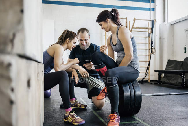 Young women and man using phone at gym — Stock Photo