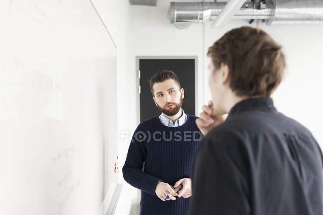 Двое мужчин стоять и говорить, доска — стоковое фото