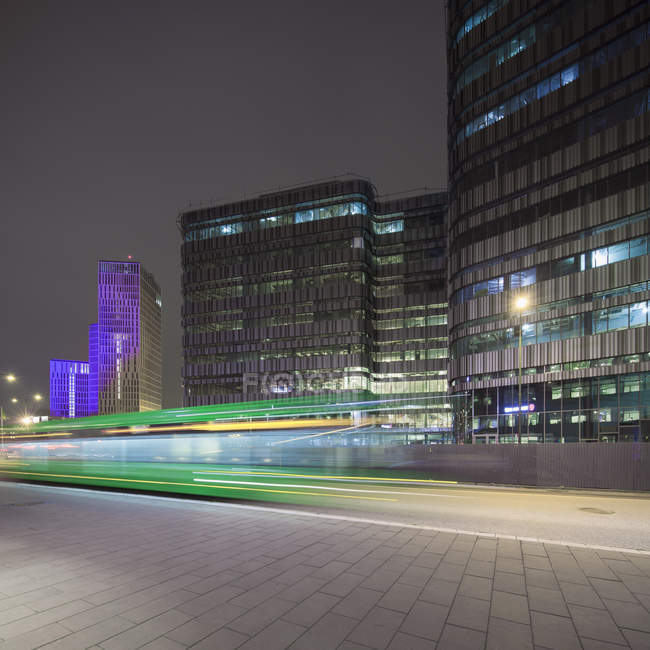Light trails and city buildings illuminated at night — Stock Photo