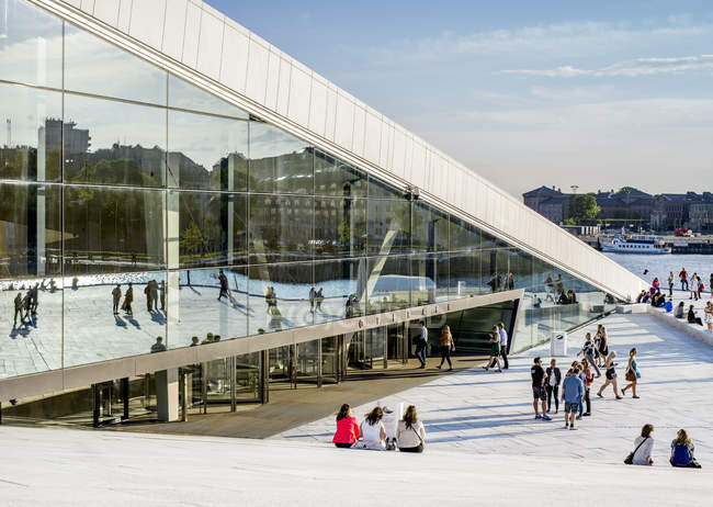Oslo Opera house with people sitting on stairs and walking on promenade at sunset — Stock Photo