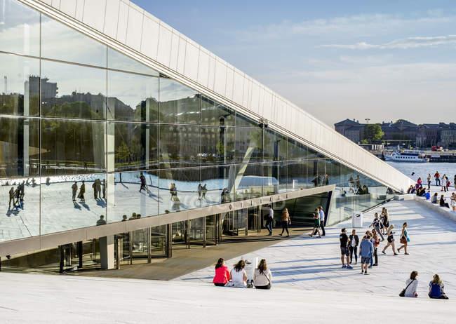 Oslo Opernhaus mit Leuten auf der Treppe sitzen und gehen auf Promenade bei Sonnenuntergang — Stockfoto