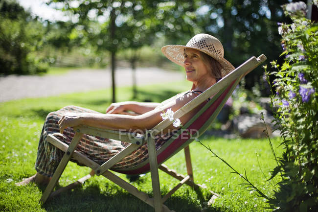 Senior woman relaxing on sun chair — Stock Photo