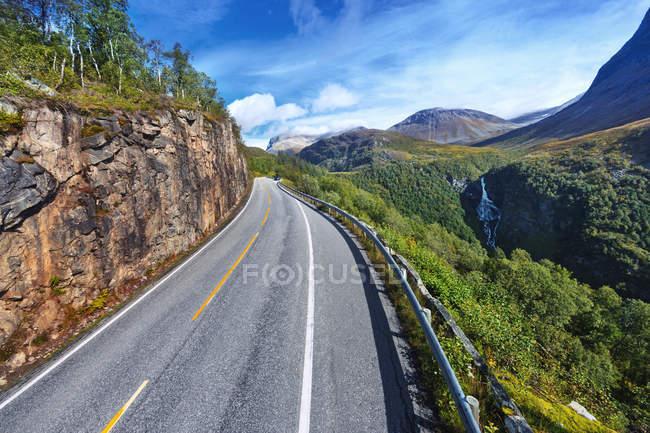 Vista da estrada na paisagem montanhosa sob céu azul nublado — Fotografia de Stock