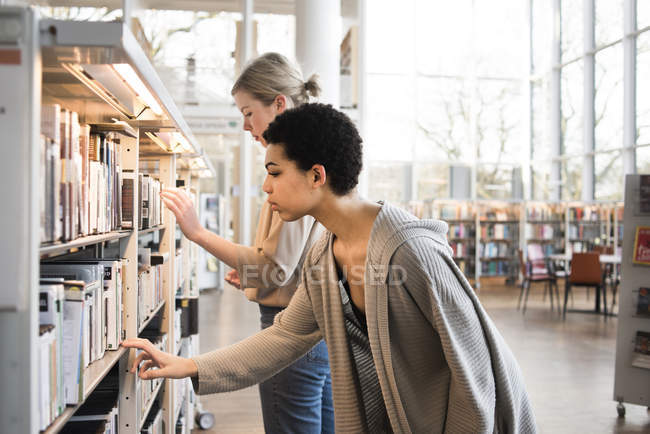 Two women choosing books in library — Stock Photo