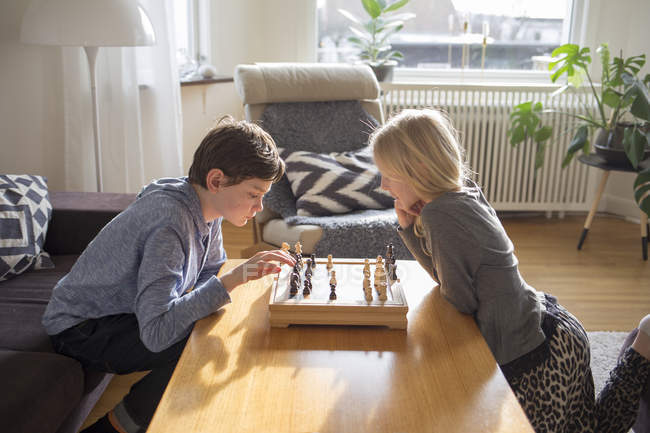 Boy and girl playing chess in living room — Stock Photo