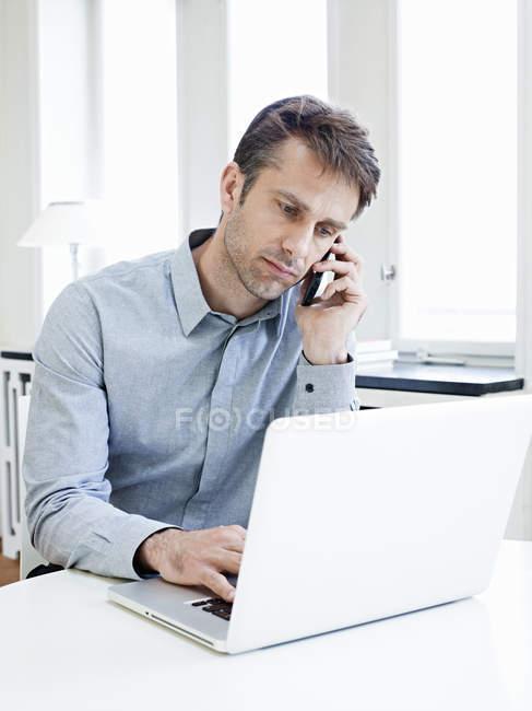 Reife Geschäftsmann mit Handy und laptop — Stockfoto