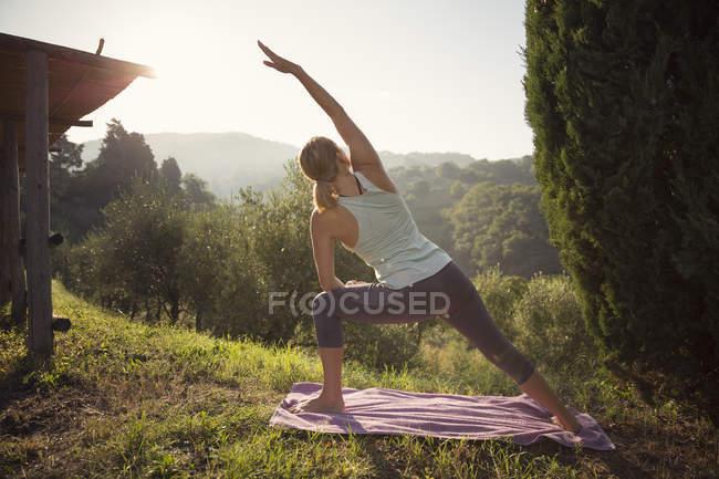Женщина практикует йогу на зеленых холмах — стоковое фото
