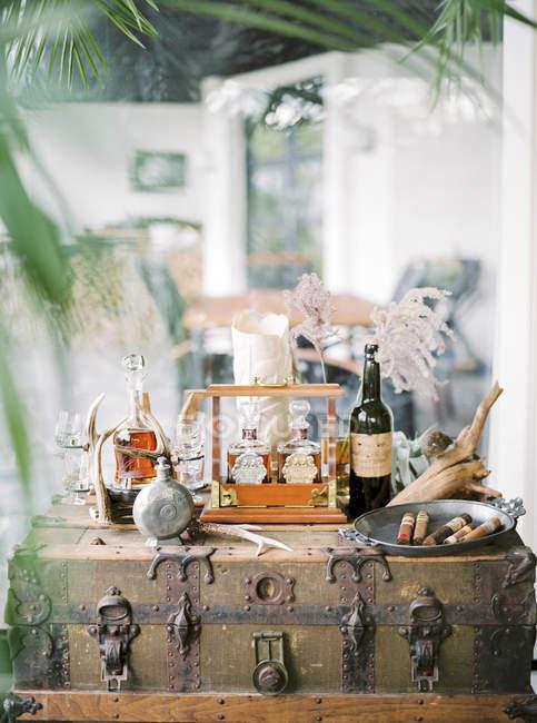 Flaschen mit Alkohol und Tablett mit Zigarren auf Koffer — Stockfoto