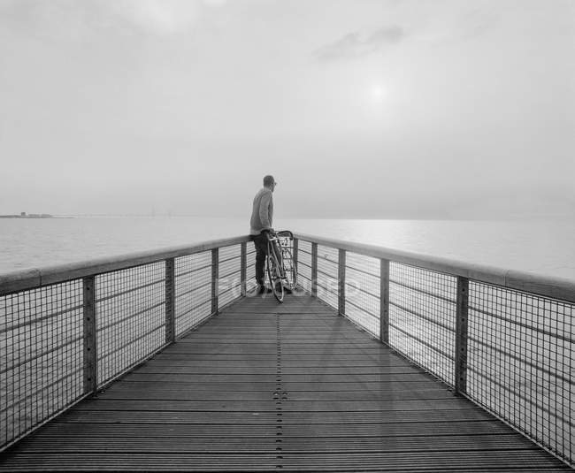 Black and white picture of man looking at view on pier — Stock Photo