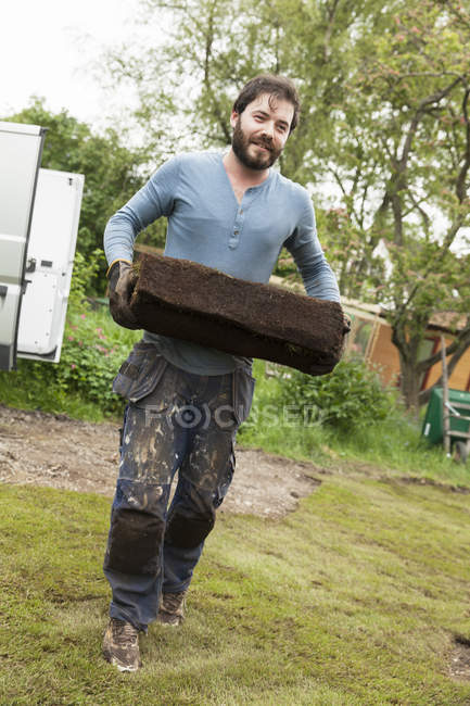 Gardener working at plant nursery and looking at camera — Stock Photo