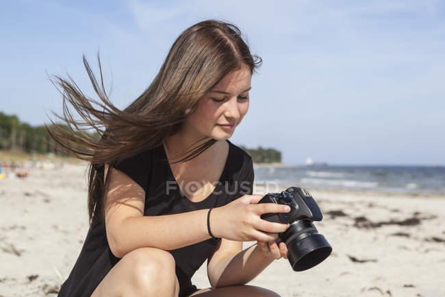 Adolescente usando câmera na praia — Fotografia de Stock