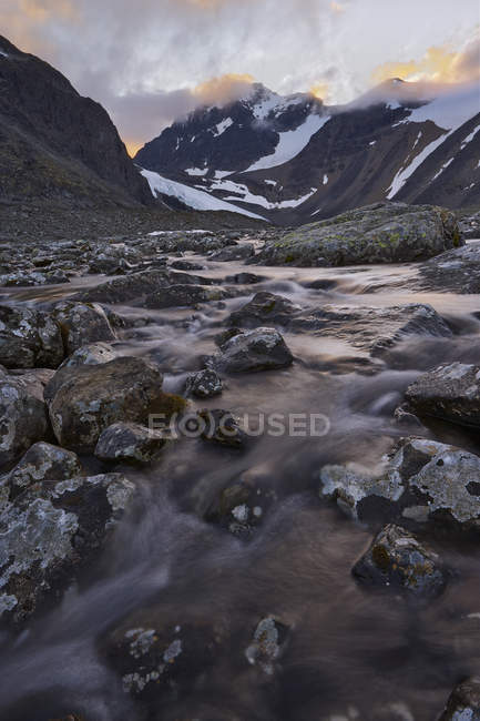 Scenic view of stream at foot of mountains at dusk — Stock Photo