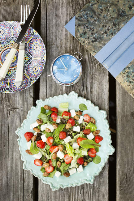 Top view of plate with salad on wooden table — Stock Photo