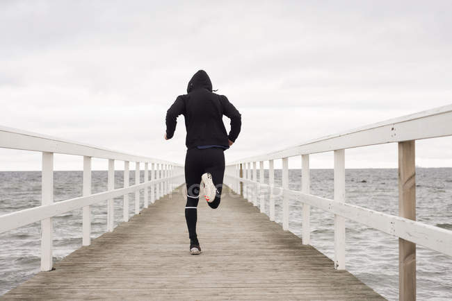 Rear view of young man running on pier — Stock Photo