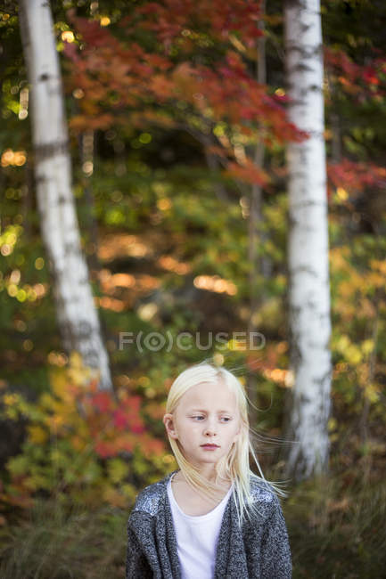 Portrait of blonde girl with autumn trees in background — Stock Photo