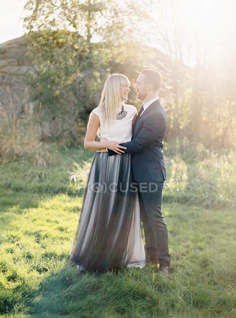 Noivo e noiva em pé juntos na grama, foco seletivo — Fotografia de Stock
