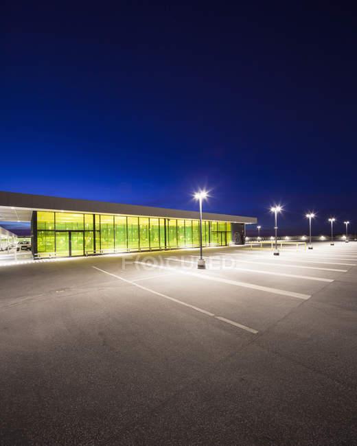 Пустой стоянке и здание, освещенной ночью — стоковое фото