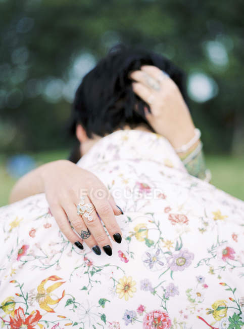 Bride and groom in shirt with floral pattern at hippie wedding, selective focus — Stock Photo