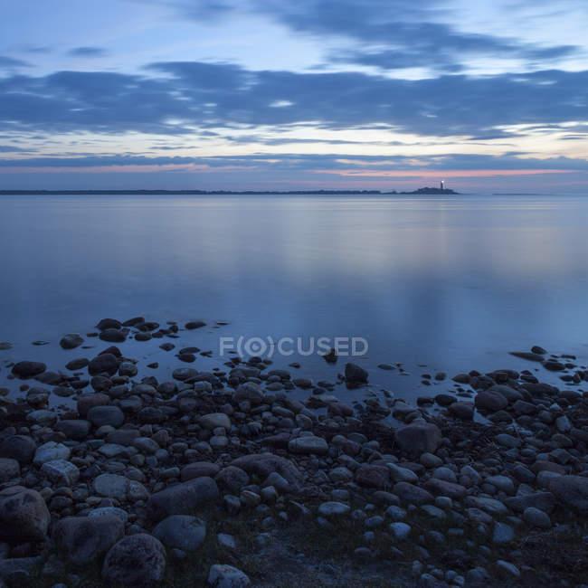 Морський пейзаж з маяк висвітлюватися в сутінках і скелястий берег — стокове фото
