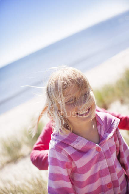 Two girls walking on beach, focus on foreground — Stock Photo