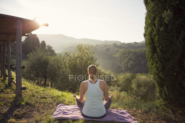 Femme en position lotus face aux collines verdoyantes — Photo de stock