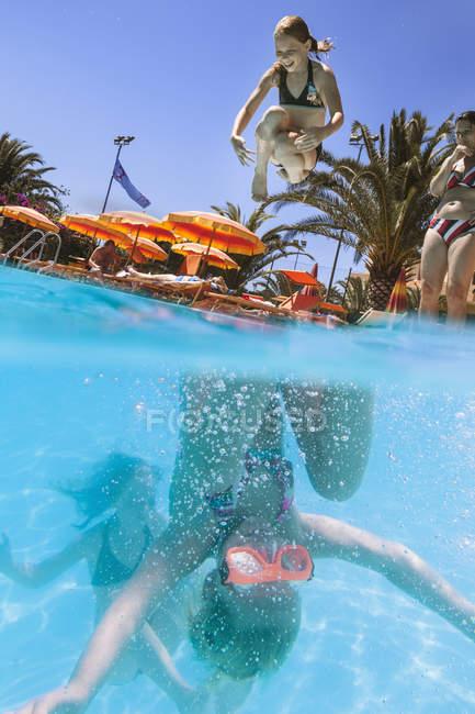 Mère regardant les enfants plonger dans la piscine — Photo de stock