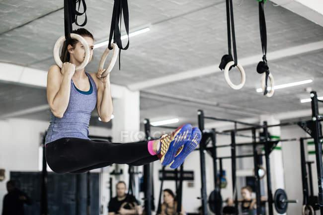 Молодая женщина тренируется на гимнастических кольцах — стоковое фото
