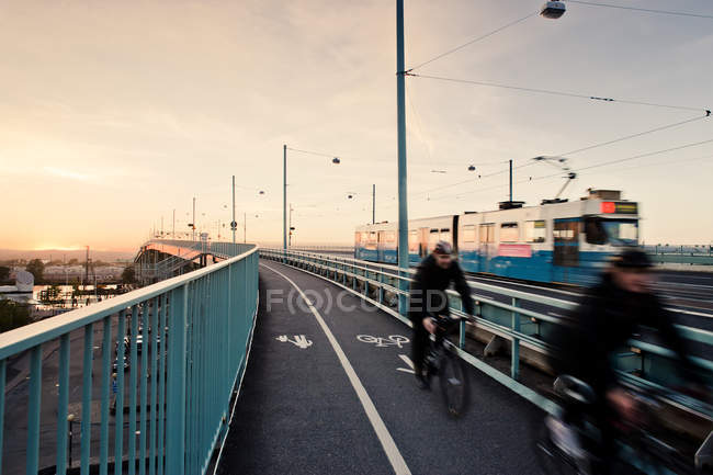 Men cycling on bridge, blurred motion — стокове фото