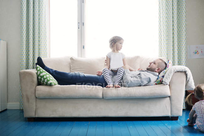 Father playing with daughters in living room — Stock Photo