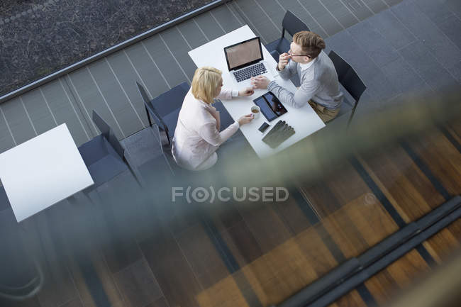 Colleagues sitting at desk and brainstorming, selective focus — Photo de stock