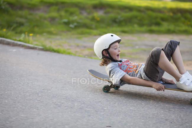 Junge rutscht mit Skateboard die Straße hinunter — Stockfoto