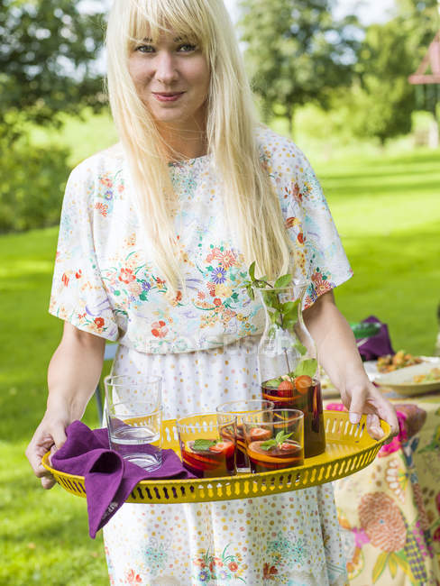 Woman holding yellow tray with sangria — Stock Photo