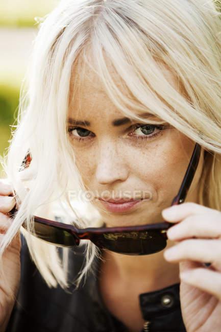 Блондинка снимает солнцезащитные очки, избирательный фокус — стоковое фото
